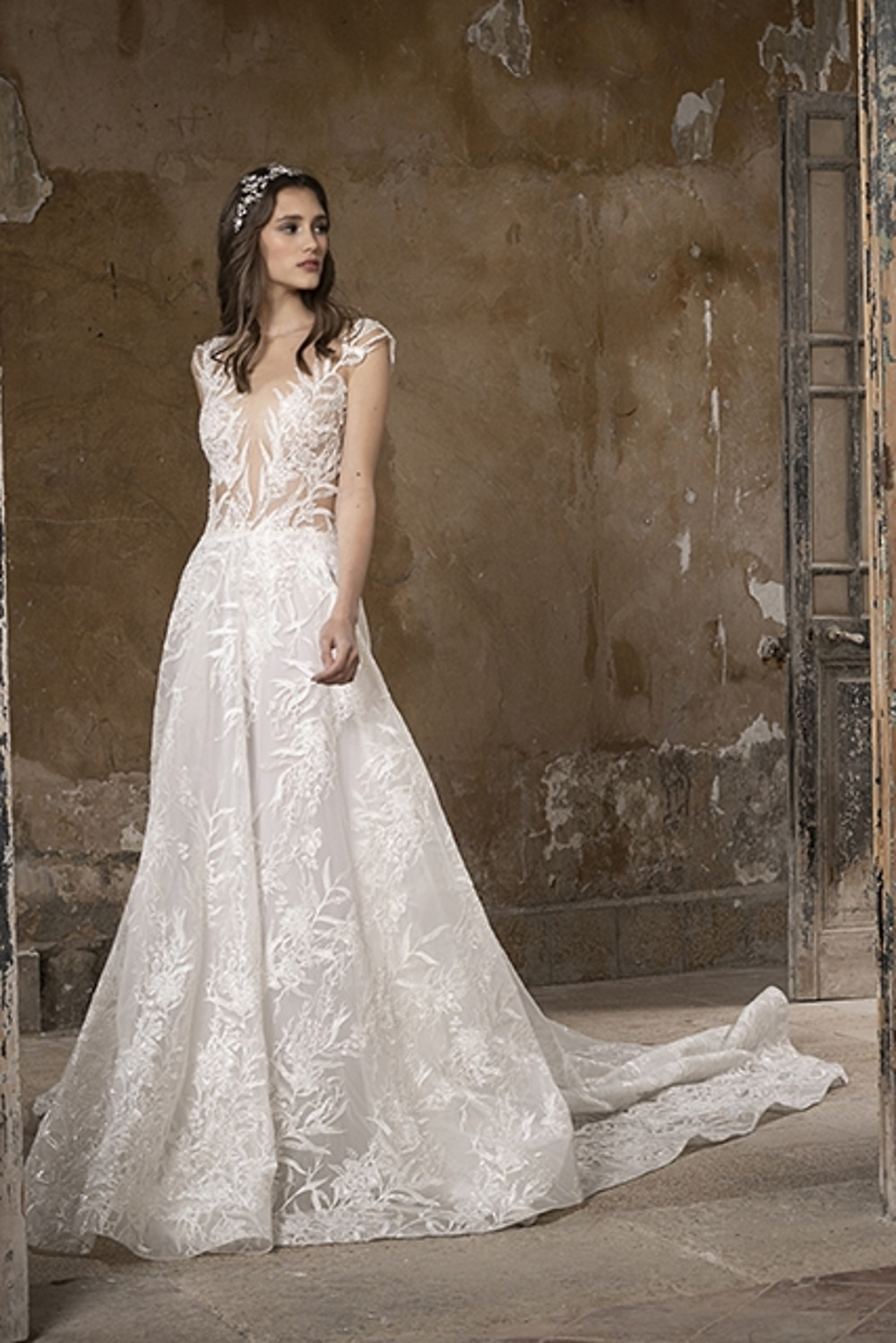 A backless wedding gown with a plunging neckline enriched with intricate embroidery and sequin detailing