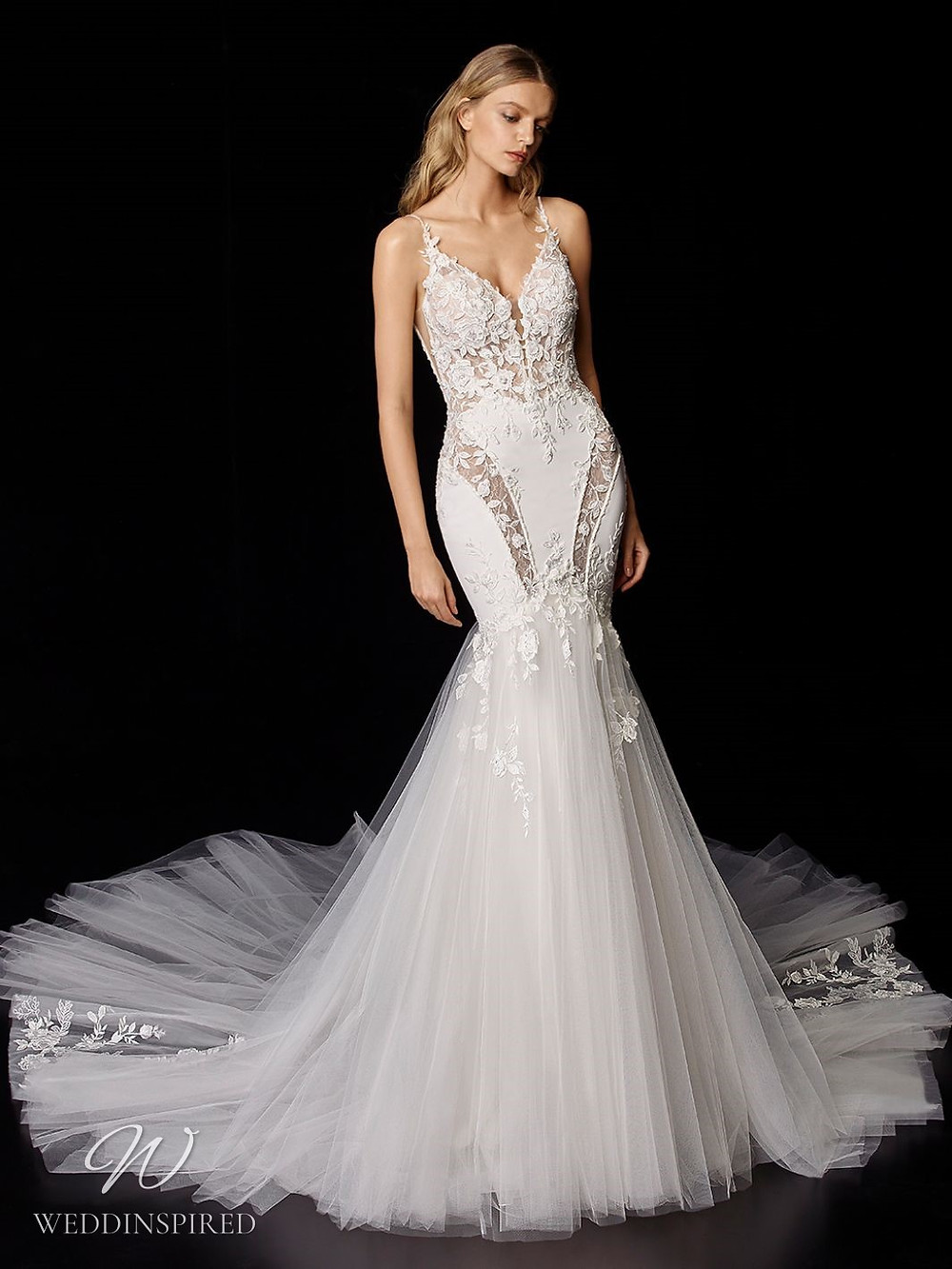 An Enzoani lace and tulle mermaid wedding dress with illusion inserts and a train