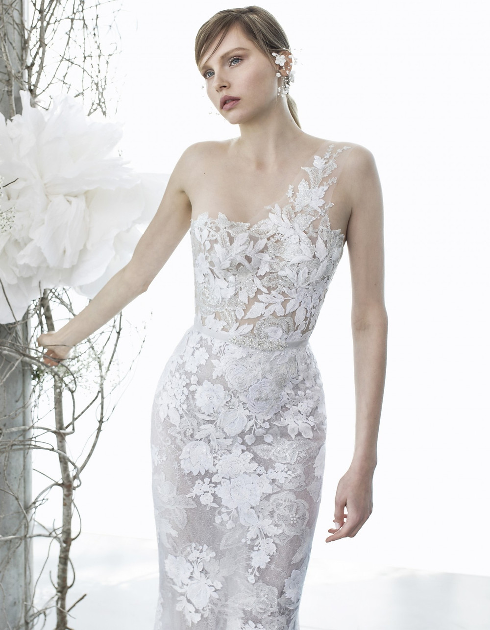 A one shoulder, sheath wedding dress with flowers and floral embellishments