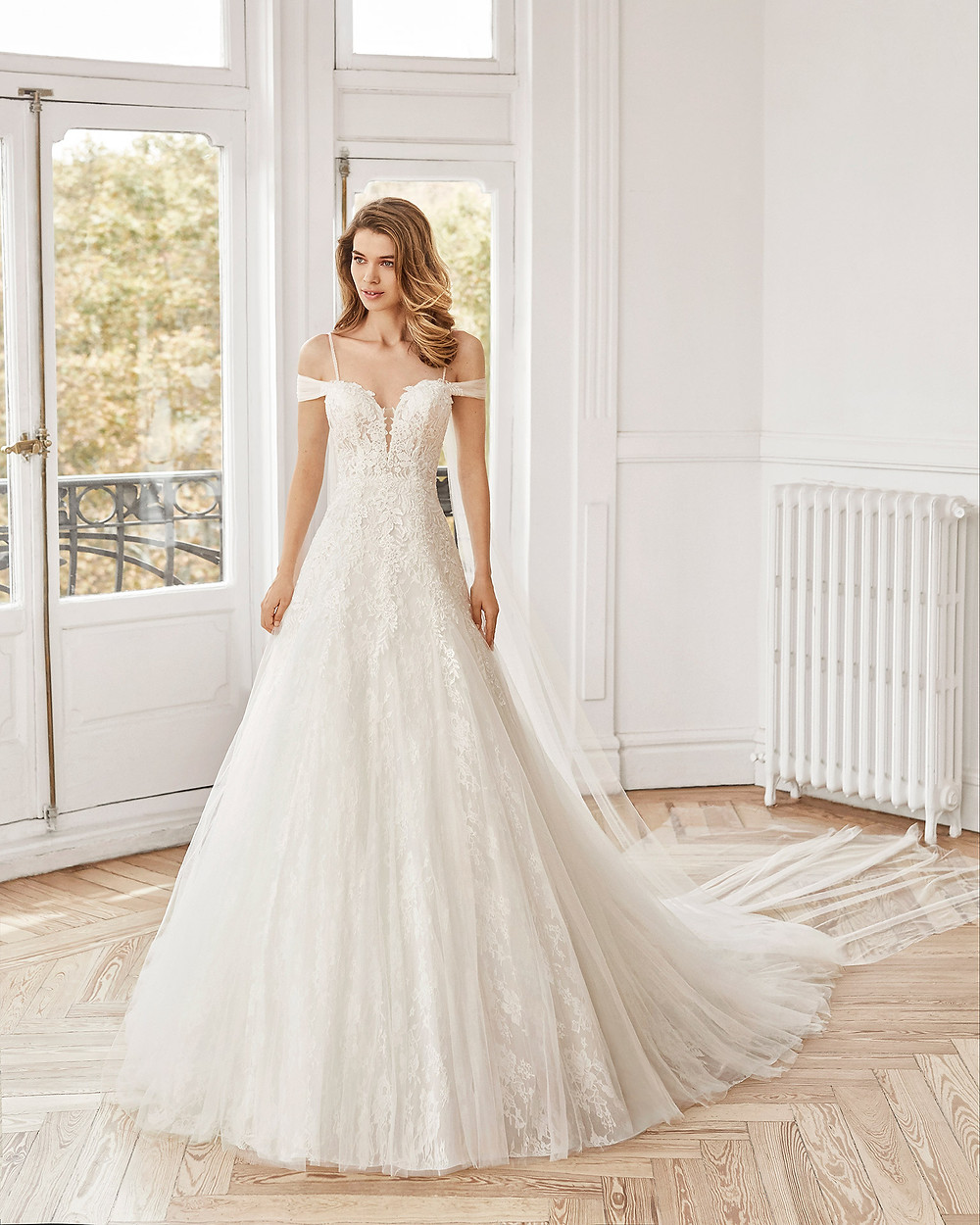 An Aire Barcelona 2020 off the shoulder lace and tulle A-line wedding dress with straps