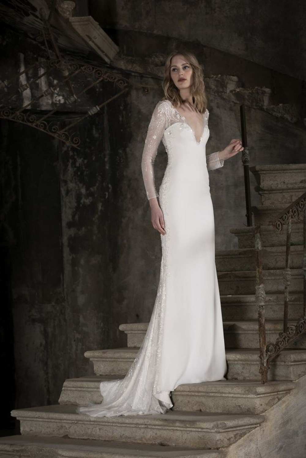 A fitted wedding dress intricately enriched with beaded embroidery, featuring a plunging neckline and long sleeves.