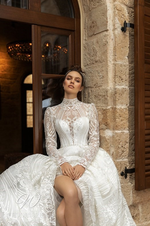 An Ida Torez 2021 modest lace and silk ball gown wedding dress with long sleeves and a high neck