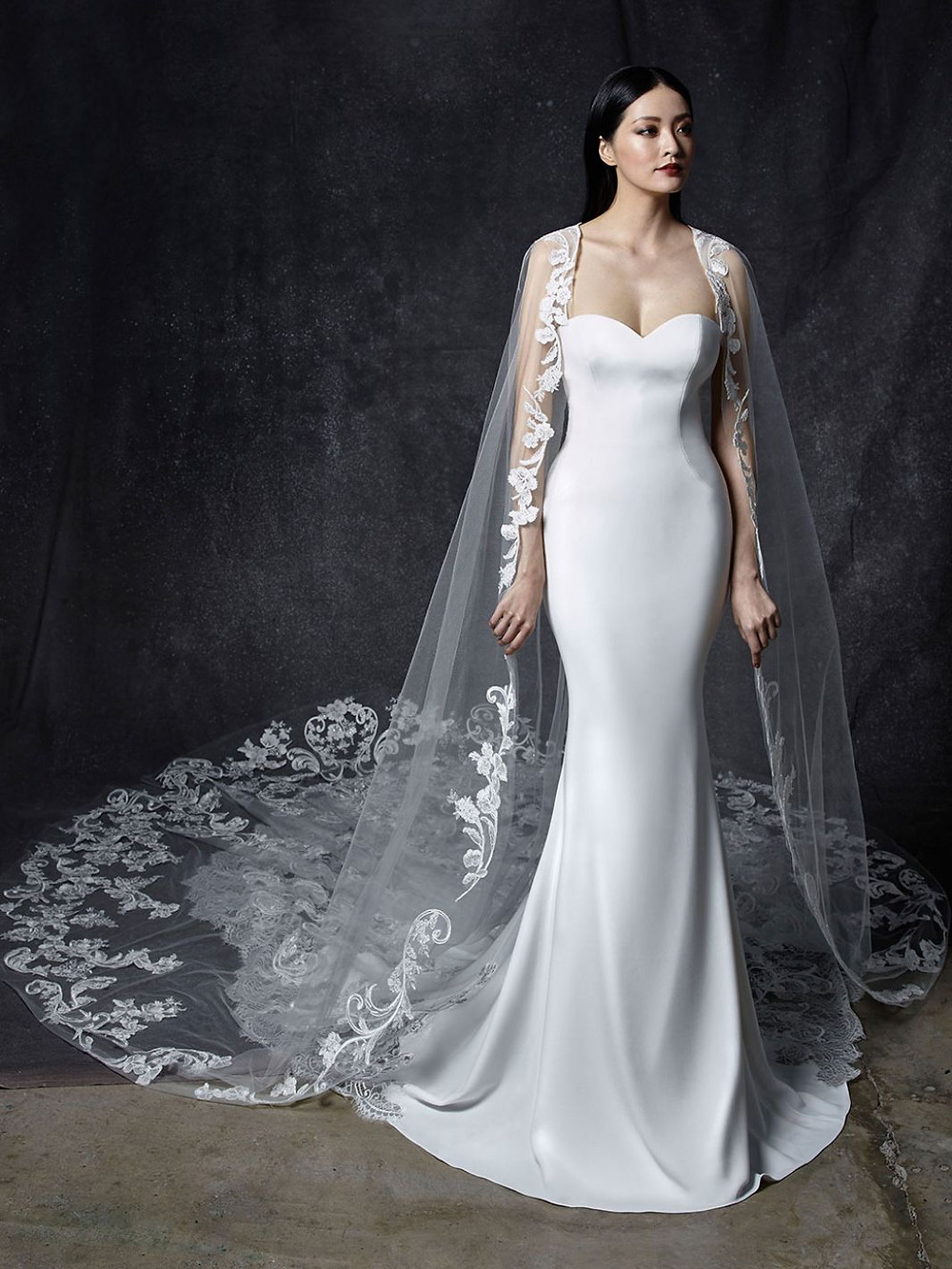 An Enzoani silk mermaid wedding dress with a sweetheart neckline and a tulle cape