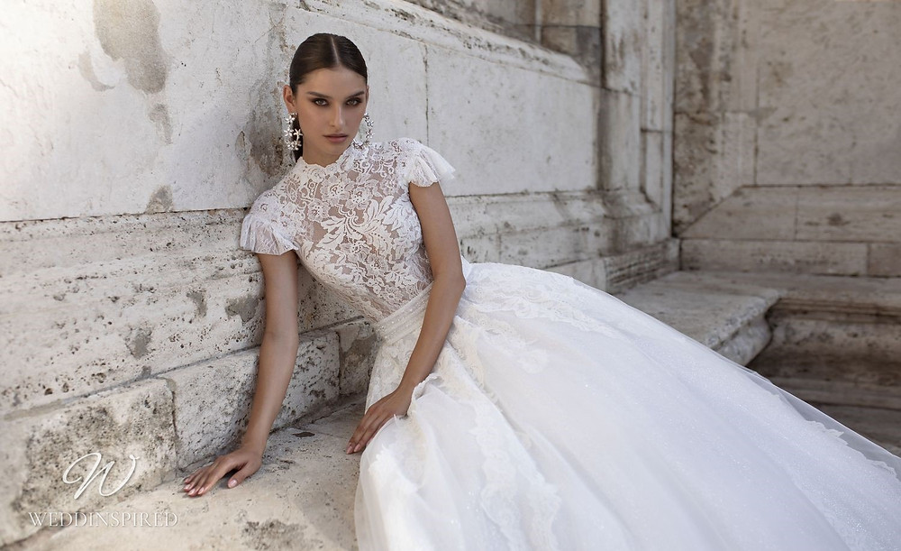 A Pinella Passaro lace ball gown wedding dress with a high neck and cap sleeves
