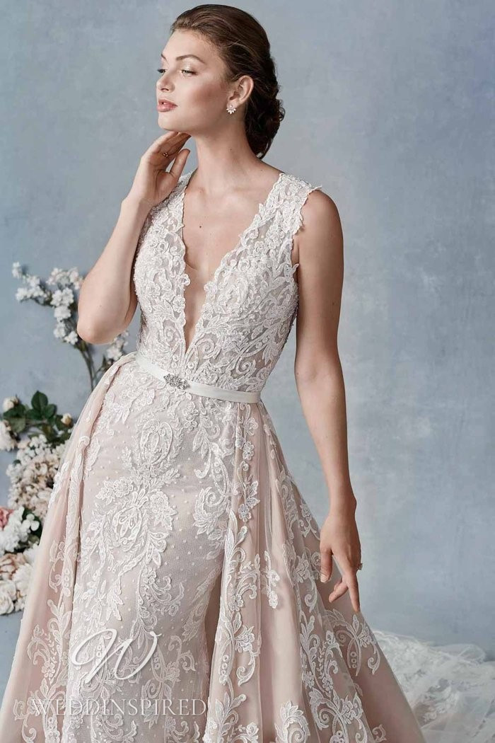 A Kenneth Winston 2021 blush lace mermaid wedding dress with a v neck and a detachable skirt