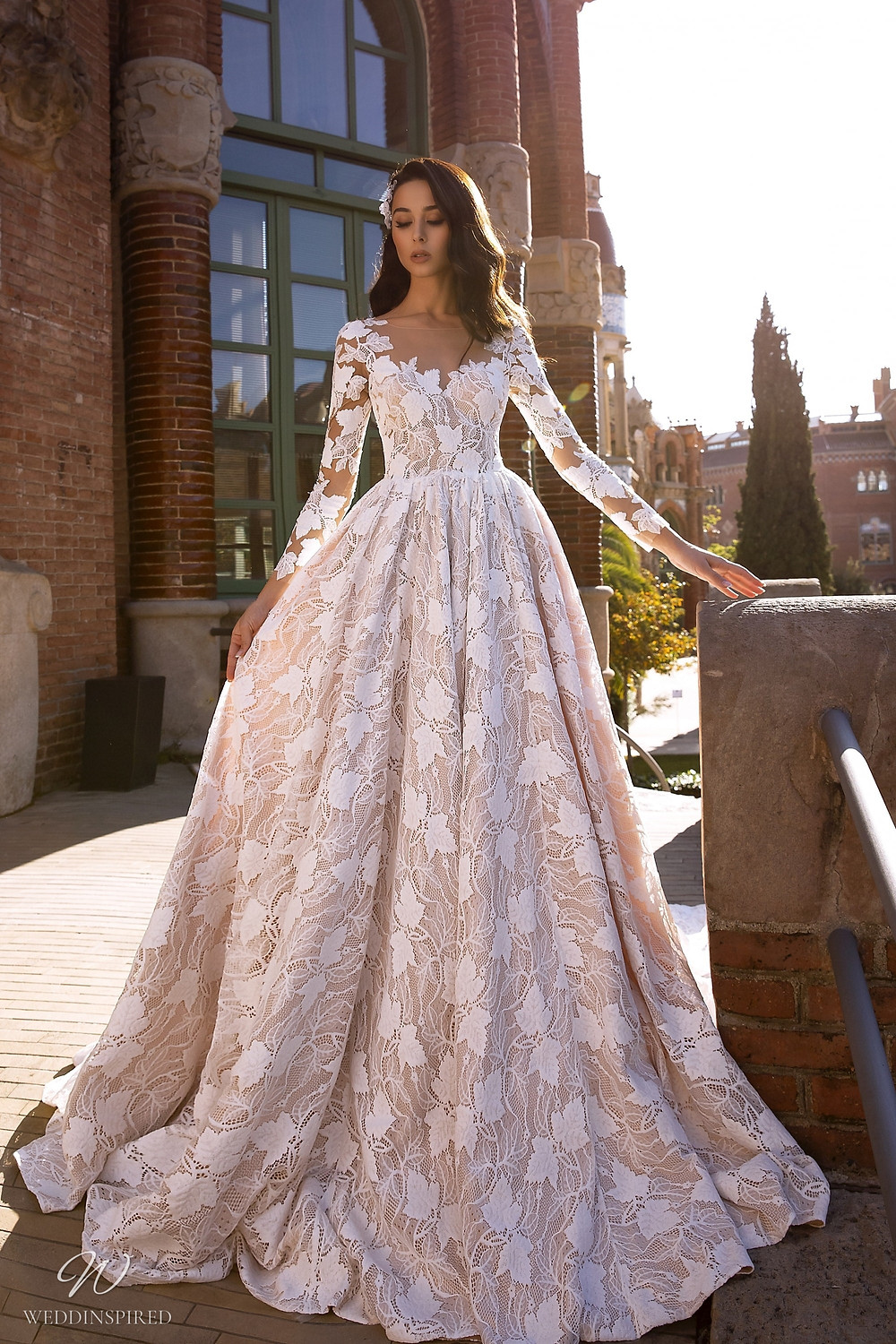 A Maks Mariano lace ball gown wedding dress with long sleeves