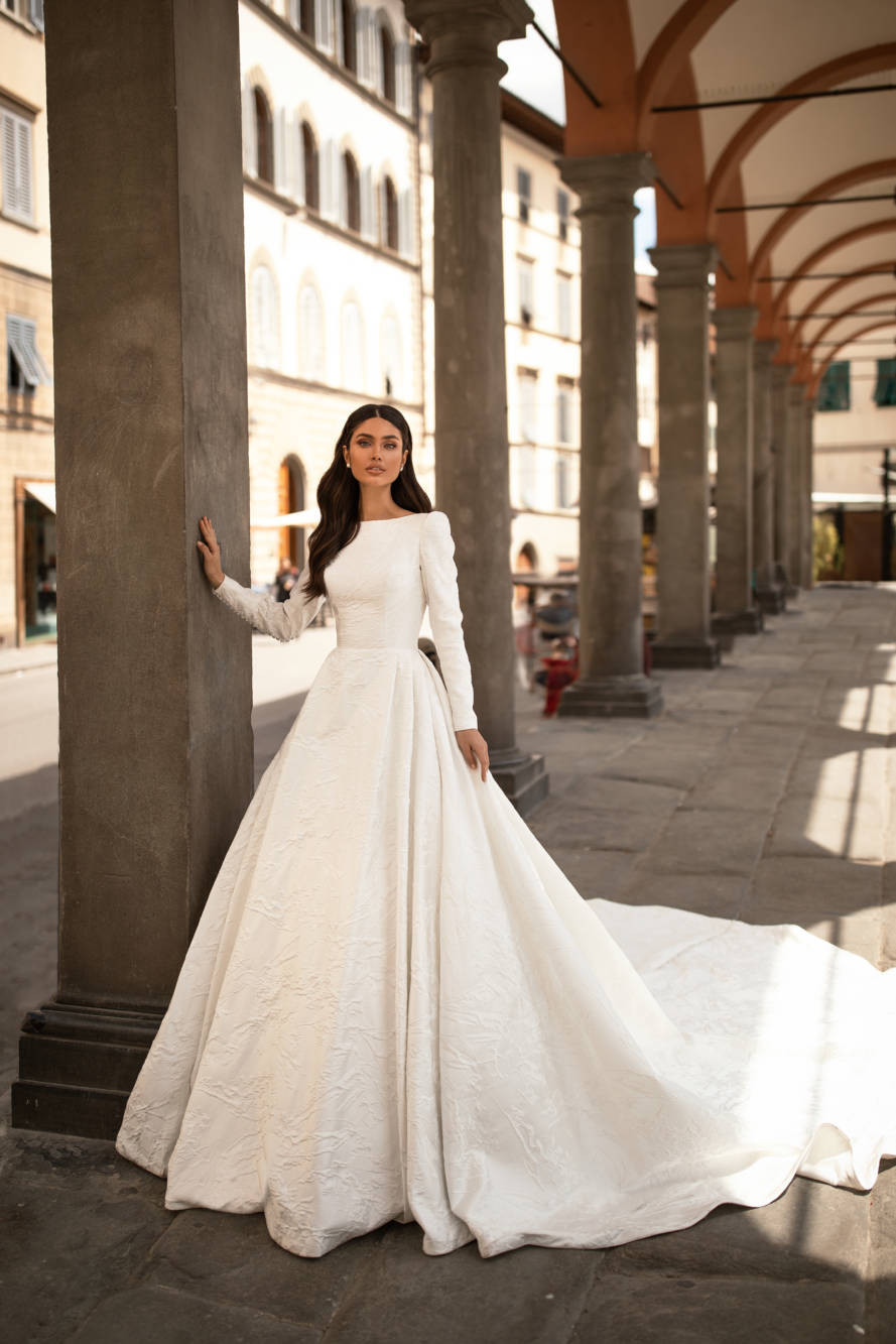 A Milla Nova modest princess ball gown wedding dress with long sleeves and a train