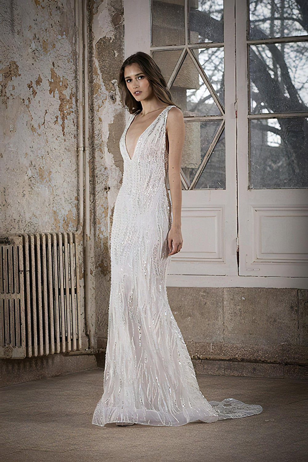 A fitted wedding gown featuring a plunging neckline and delicate embroidery