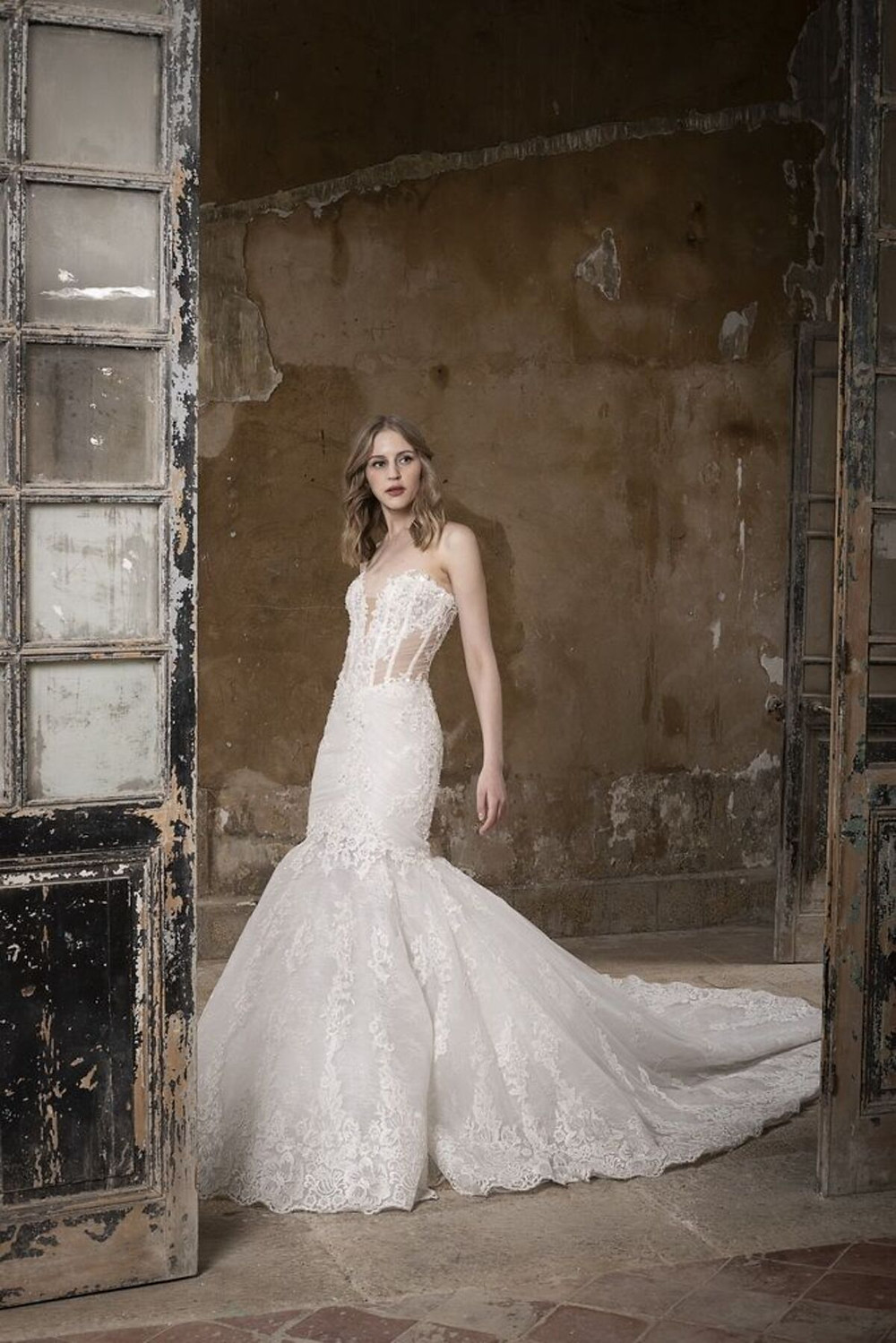 A mermaid wedding dress with a corset bodice made of tulle and french lace, featuring a statement train