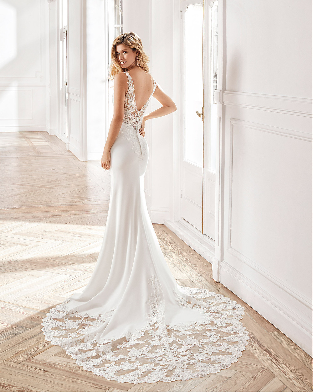 An Aire Barcelona 2020 lace and crepe mermaid fit and flare wedding dress with a low back and a train