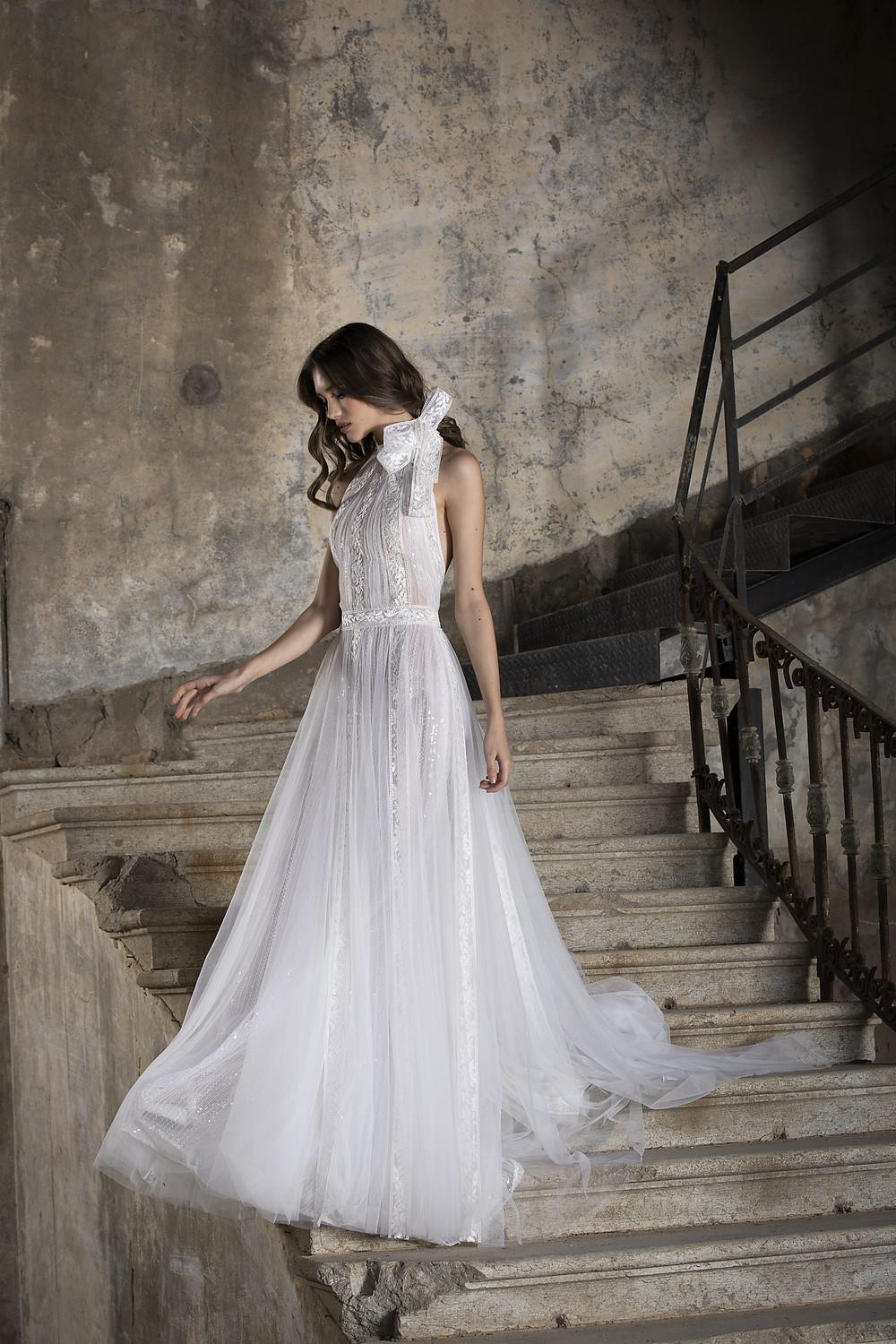 An A-line tulle wedding gown, with a bow neckline, high collar and an open back, enriched with lace strips and subtle sequined embroideries layered underneath the tulle
