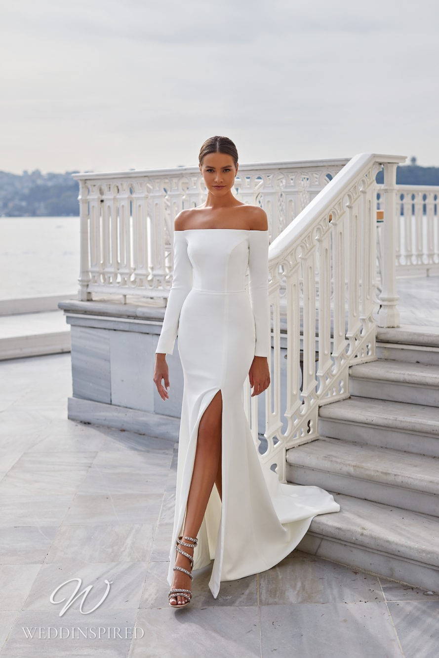 A Milla Nova 2021 off the shoulder satin mermaid wedding dress with long sleeves and a slit