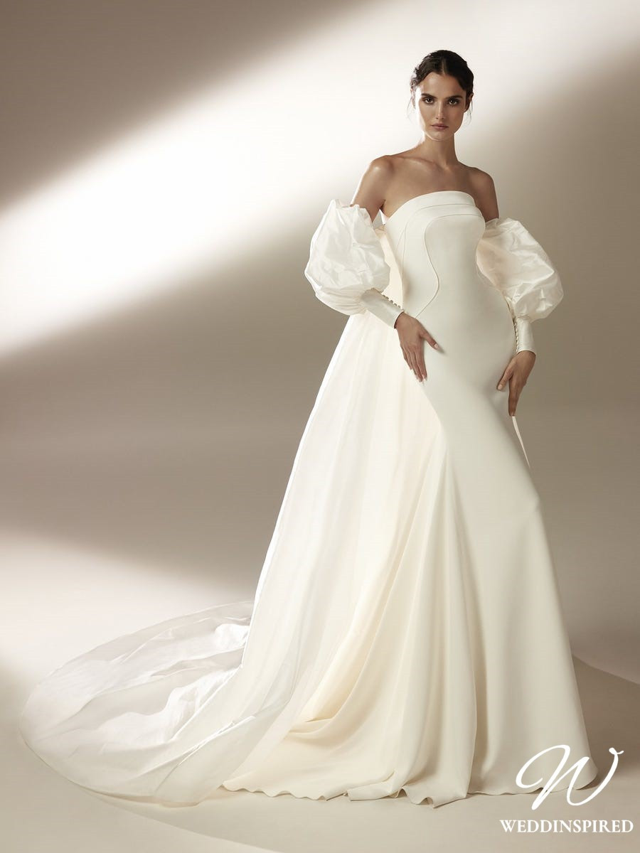 An Atelier Pronovias strapless silk sheath wedding dress with detachable puff sleeves and a cape