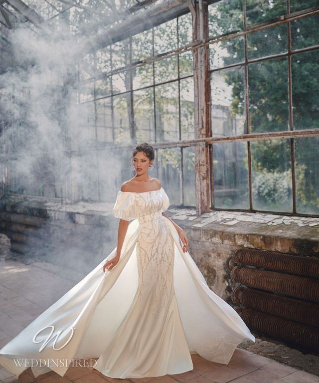 An Ange Etoiles 2021 off the shoulder silk mermaid wedding dress with a cape