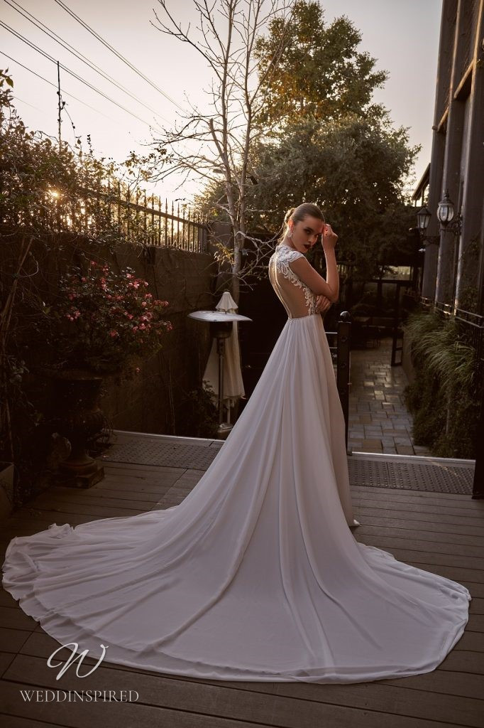 A Julie Vino 2021 ivory lace and chiffon A-line wedding dress with cap sleeves and an open back