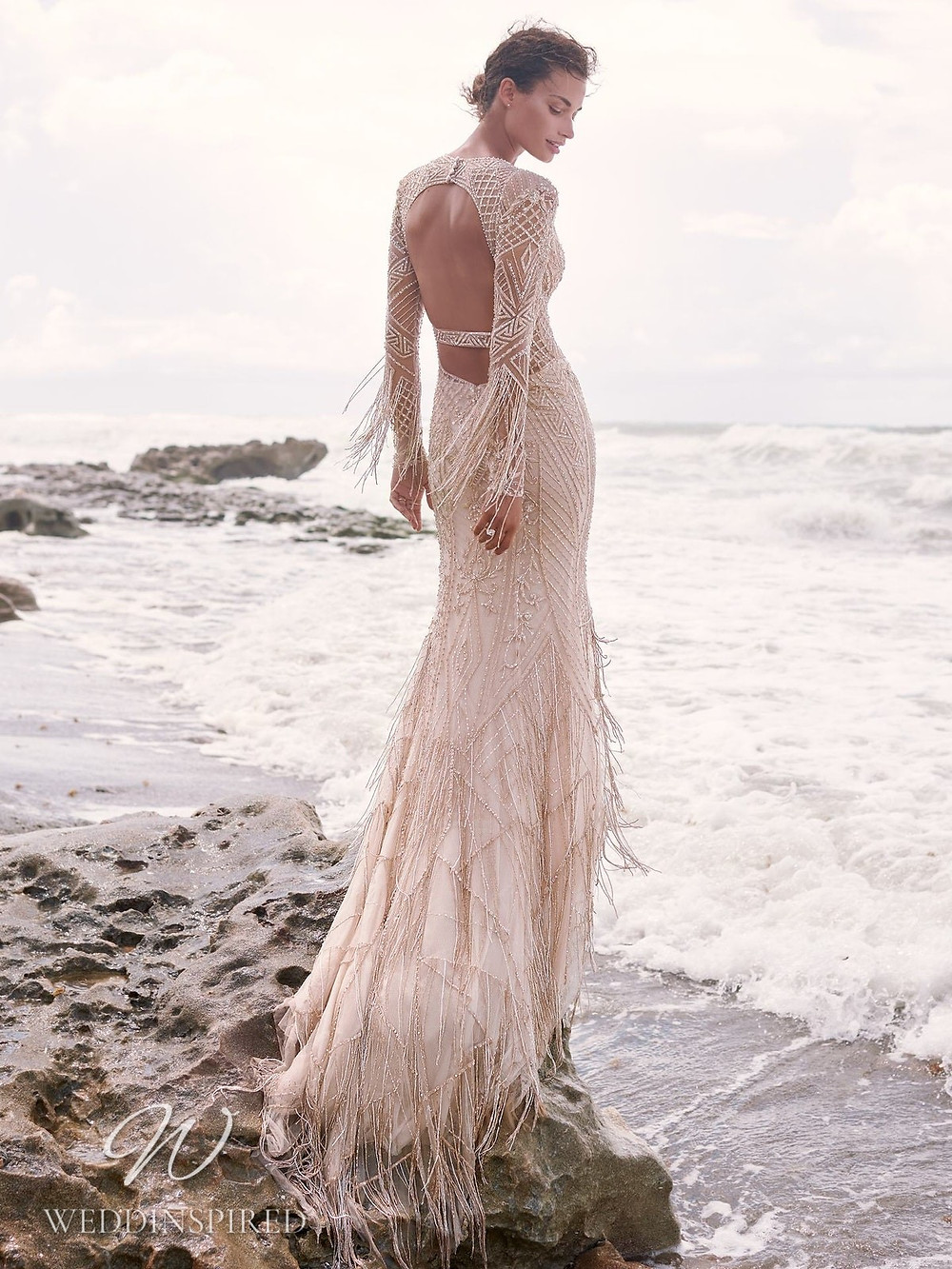 A Sottero & Midgley Spring 2021 champagne mermaid dress with fringe, long sleeves and a keyhole back