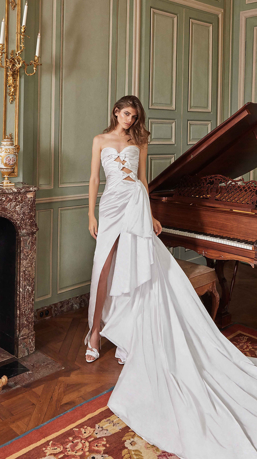 A dramatically draped ball gown wedding dress with cutouts and silk bows, this asymmetrical stunner features a high slit and a side bow in a soft silk duchess satin