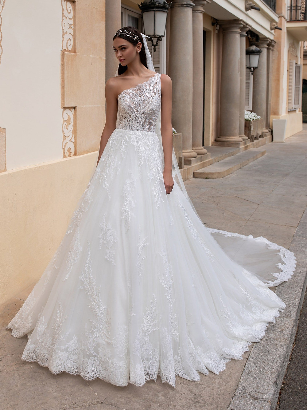 A Pronovias one shoulder, ball gown wedding dress with lace detail