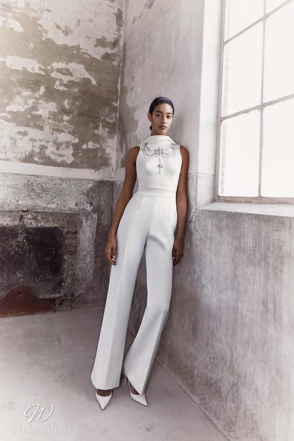 A Viktor & Rolf Fall/Winter 2021 simple white wedding pantsuit or jumpsuit with a high neckline