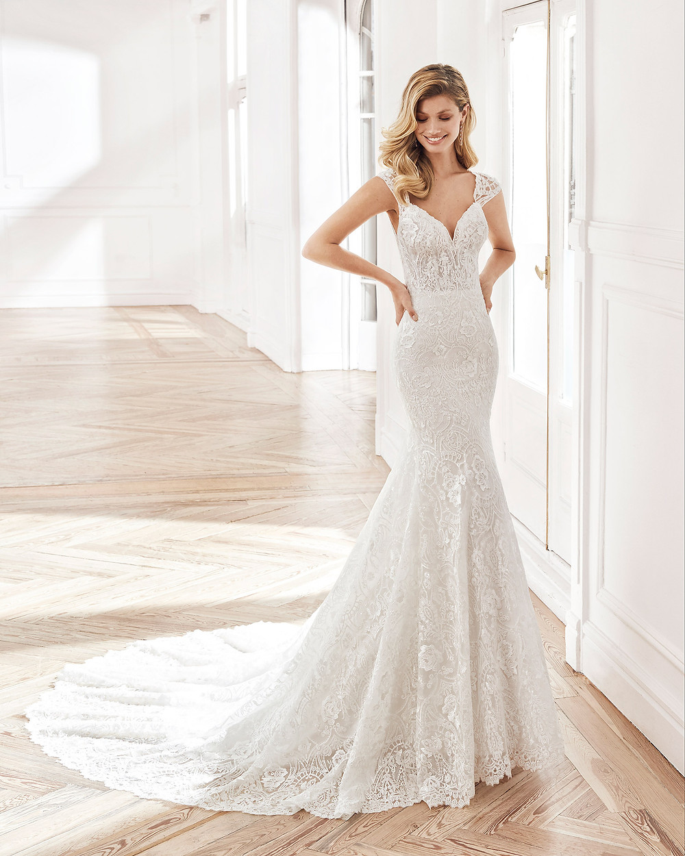 An Aire Barcelona 2020 lace mermaid fit and flare wedding dress with cap sleeves