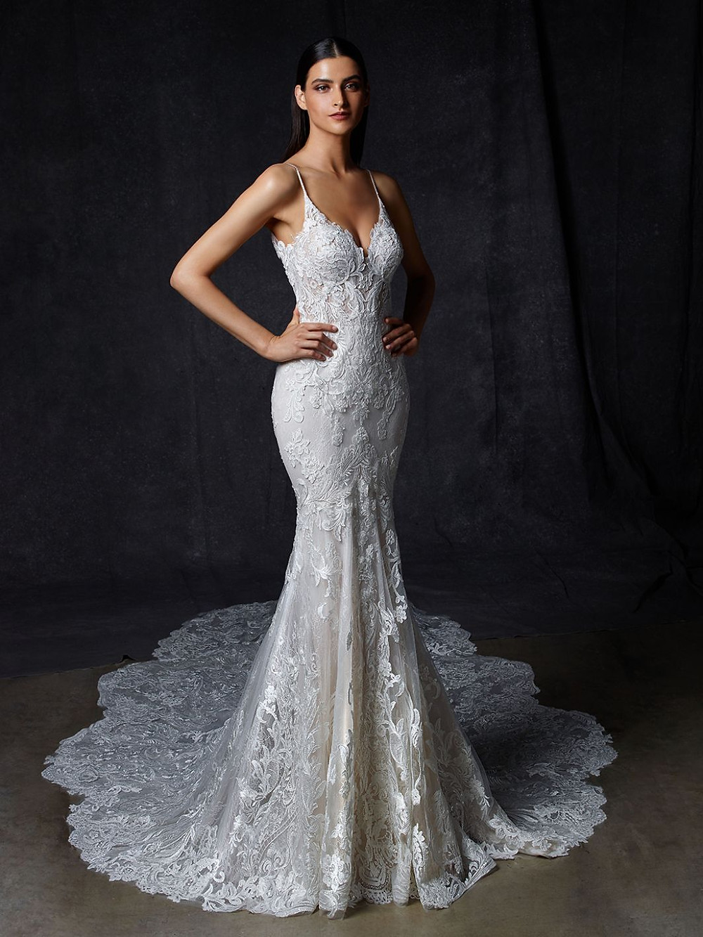 An Enzoani lace mermaid wedding dress with thin straps and a long train