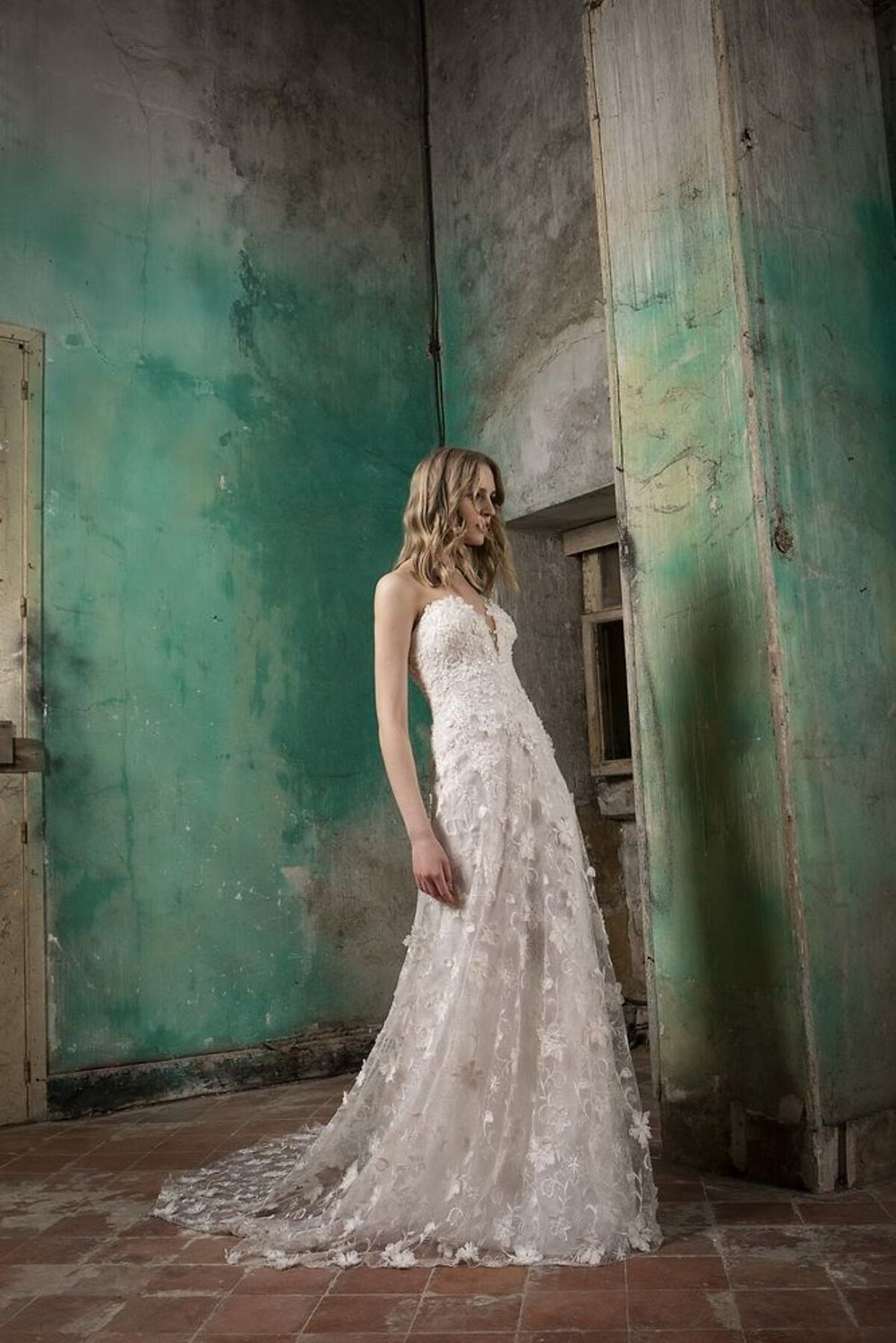A flared wedding dress made of lace enriched with 3-dimensional flowers