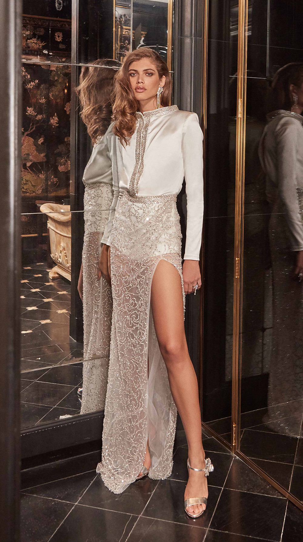 Chic and sultry, this stretch silk short wedding jumpsuit features a plunging raised collar trimmed with glamorous hand-embroidered swarovski crystals paired with a sheer skirt covered in swirling luxe hand-beaded motifs