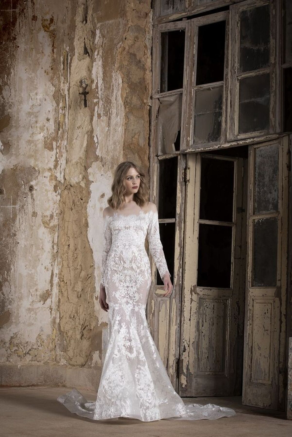 An off-shoulder illusion backless mermaid wedding gown featuring embroidered tulle and sequin embellishments