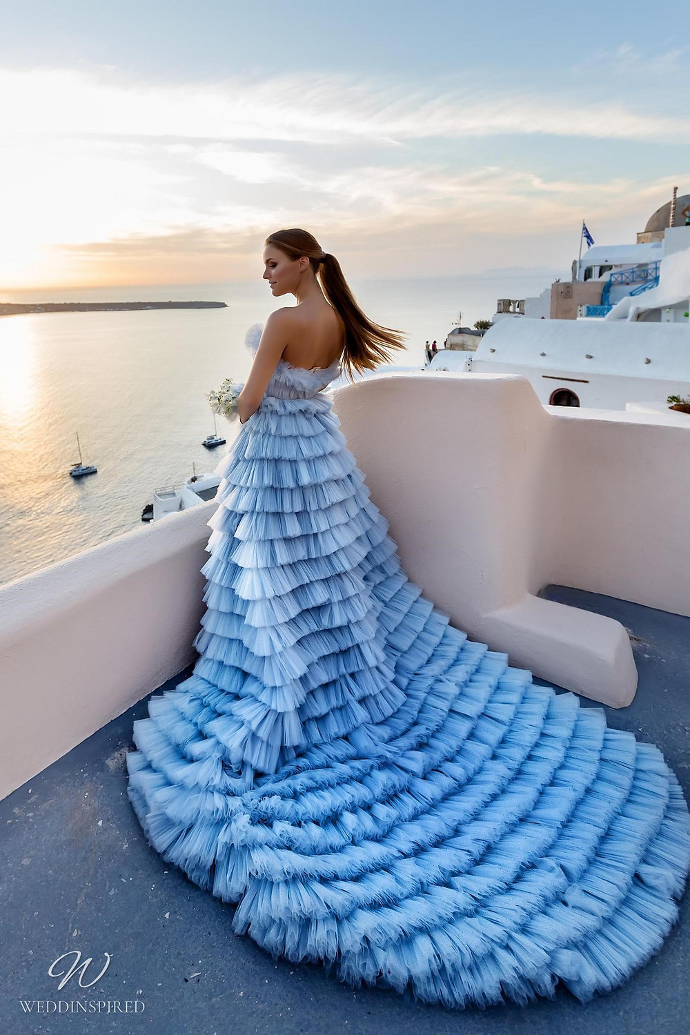 A Ricca Sposa blue strapless Cinderella ball gown wedding dress with a tulle ruffle skirt