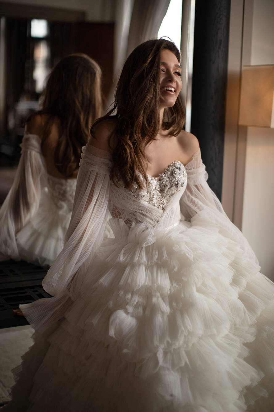 An off the shoulder chiffon ball gown wedding dress with corset, ruffle skirt and long sleeves