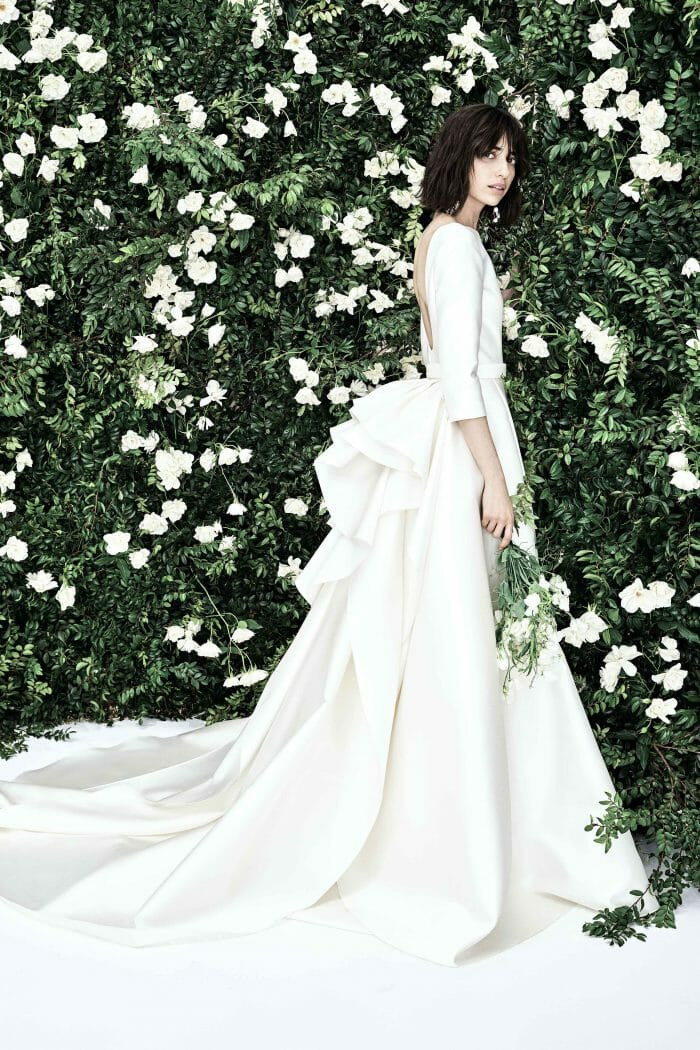 A Carolina Herrera 3/4 sleeve, ball gown wedding dress, with a low back and a large bow