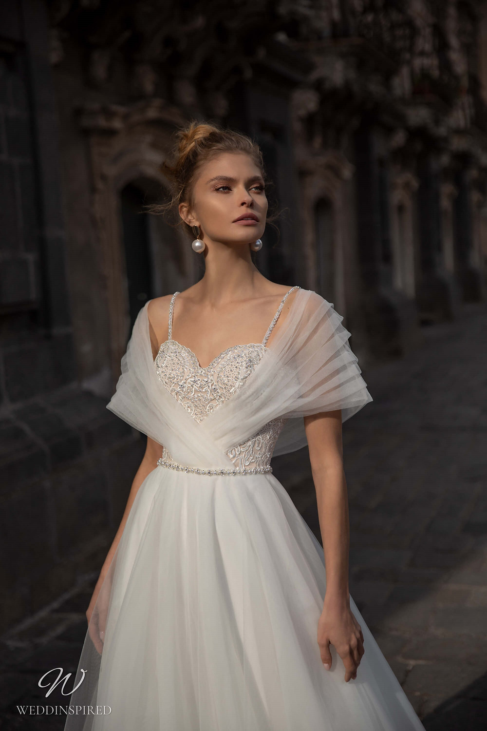 A Naviblue lace and tulle A-line wedding dress with straps and beading