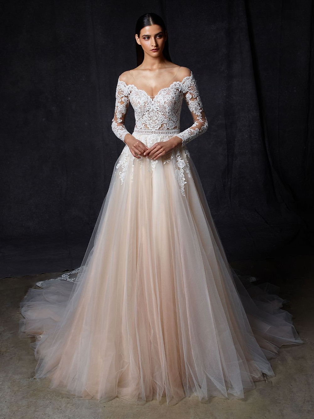 An Enzoani blush, off the shoulder A-line wedding dress with long lace sleeves and a tulle skirt