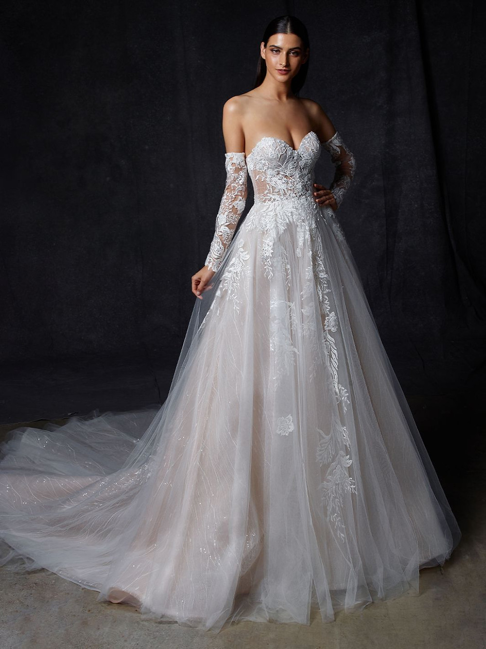 An Enzoani off the shoulder, lace and tulle ball gown wedding dress with lace gloves and a light pink skirt