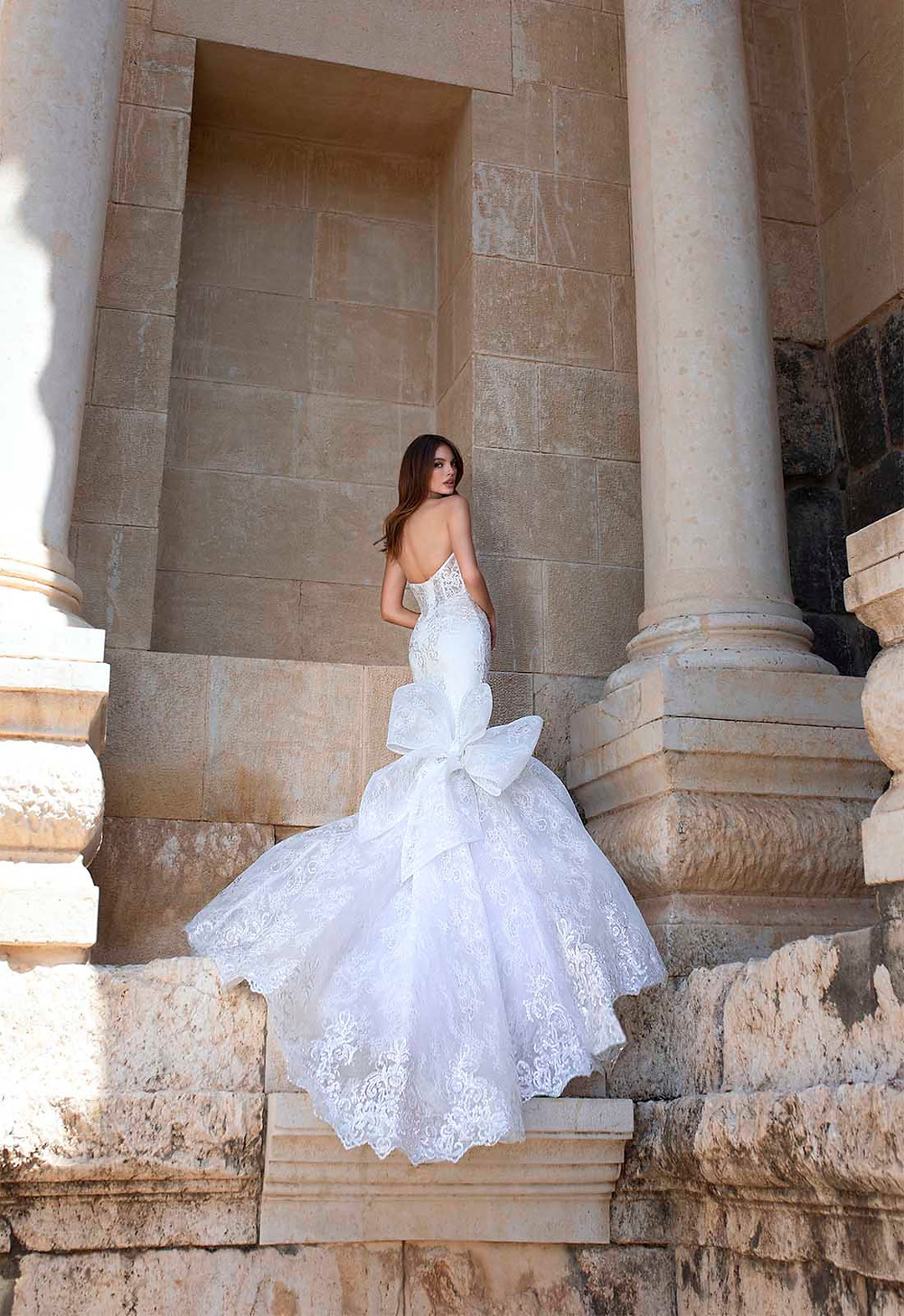 A Pnina Tornai strapless lace mermaid fit and flare wedding dress with a bow