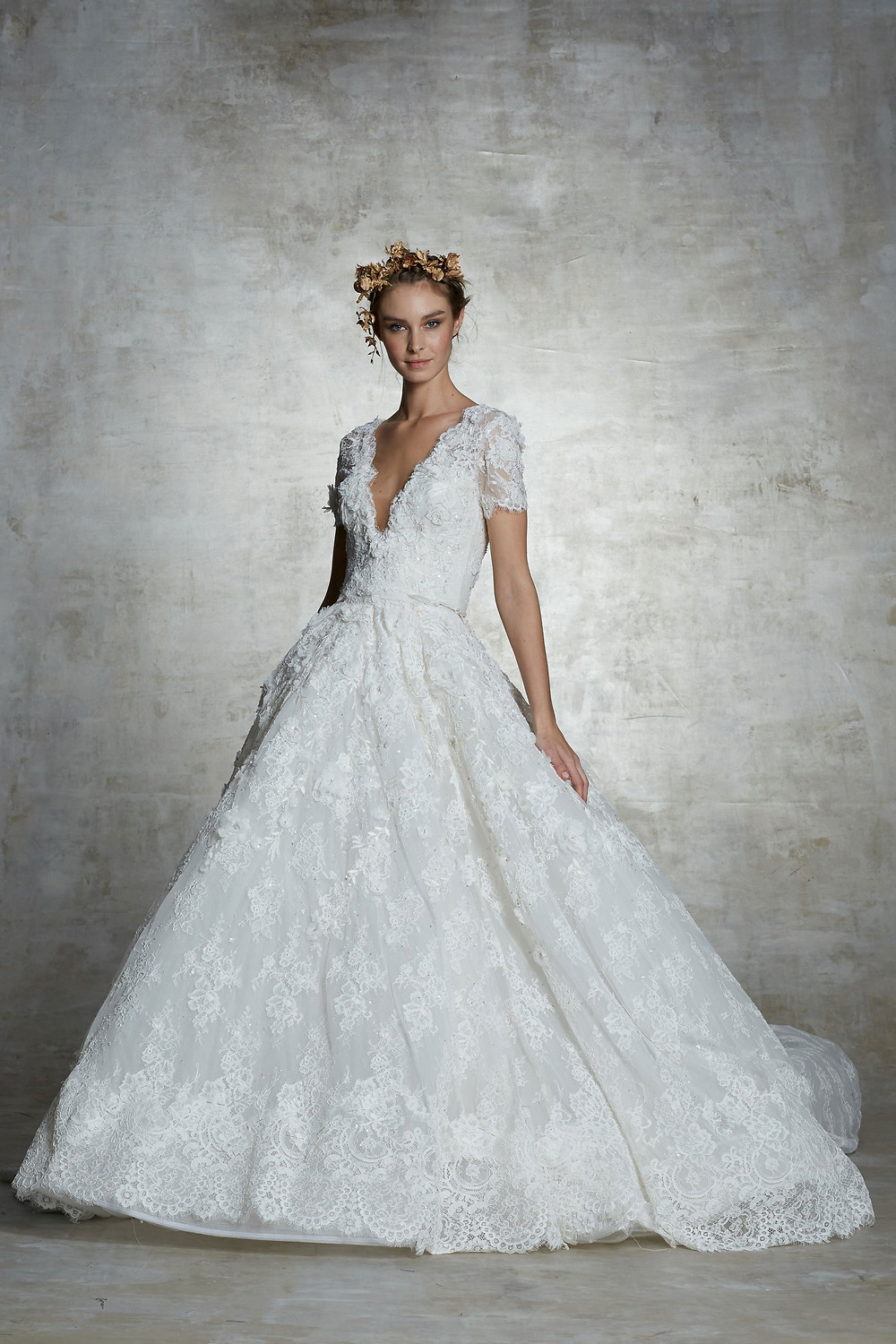 A Marchesa lace ball gown wedding dress with cap sleeves and a v neckline