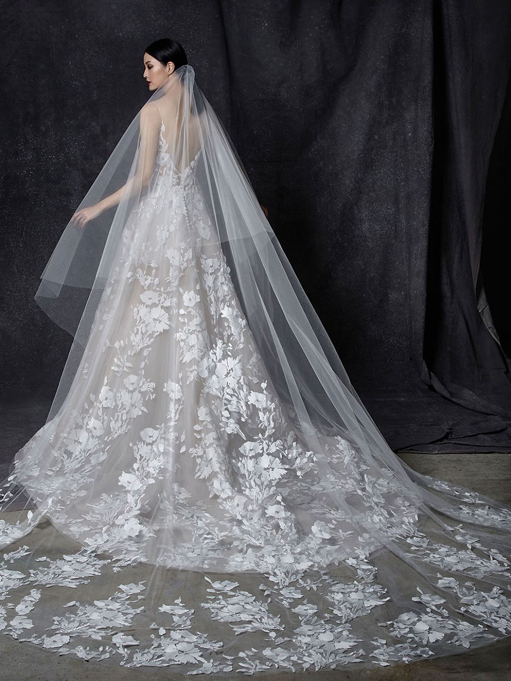 An Enzoani ball gown wedding dress with thin straps, floral print and a tulle veil