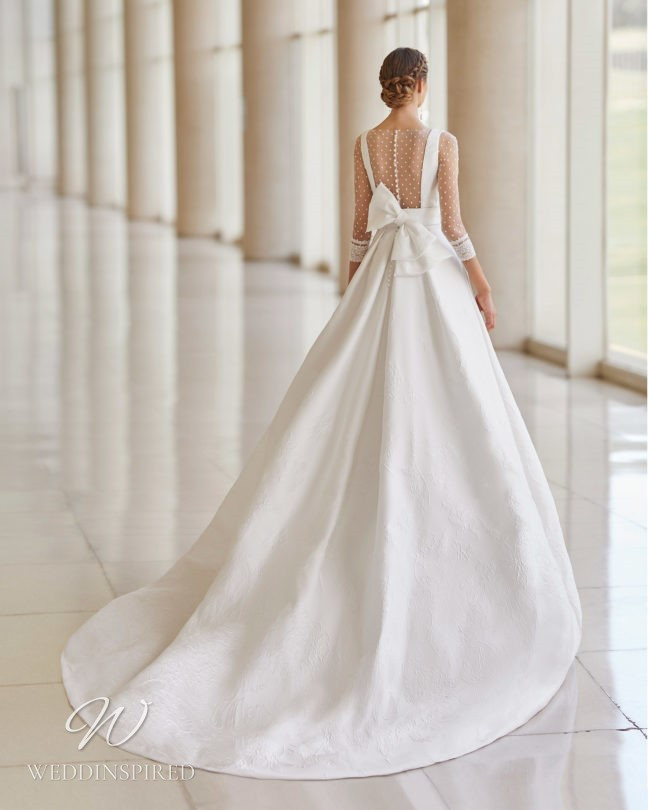 An Aire Barcelona 2021 lace ball gown wedding dress with half sleeves and a bow