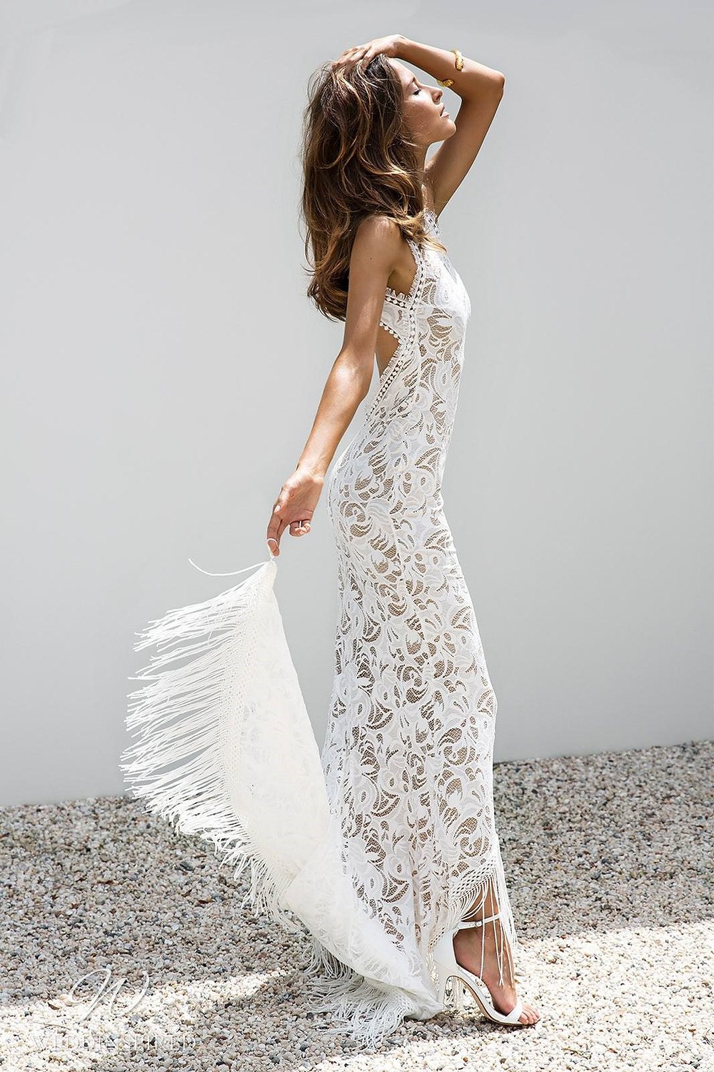 A Grace Loves Lace fitted lace mermaid wedding dress with a fringe train and an open back with a high neckline