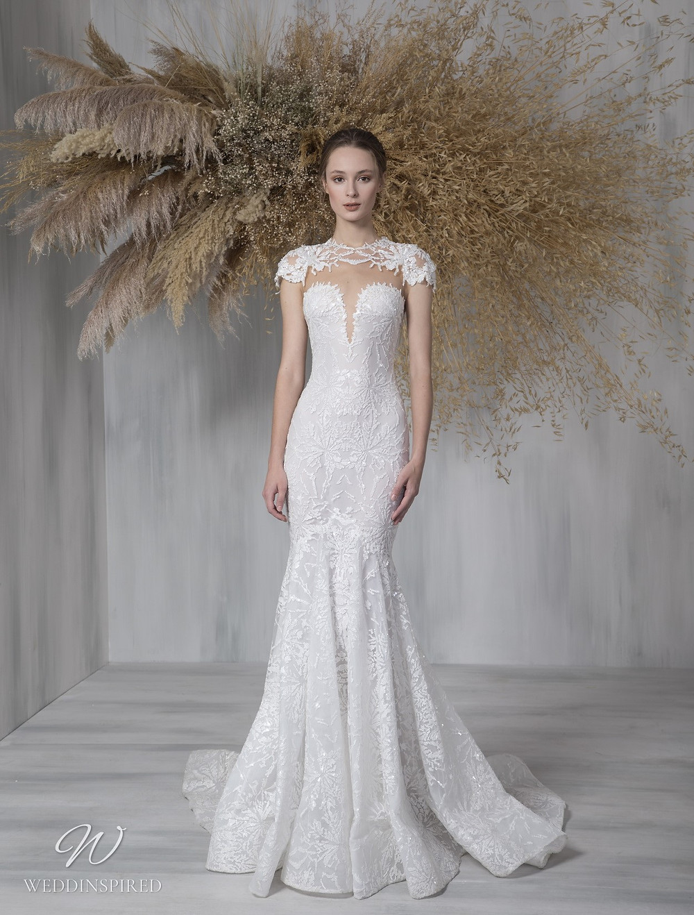 A Tony Ward 2021 lace mermaid wedding dress with an illusion top and cap sleeves