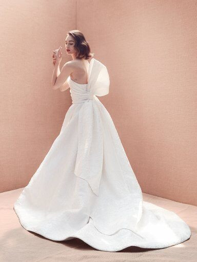 An Oscar de la Renta strapless crepe ball gown wedding dress with a bow