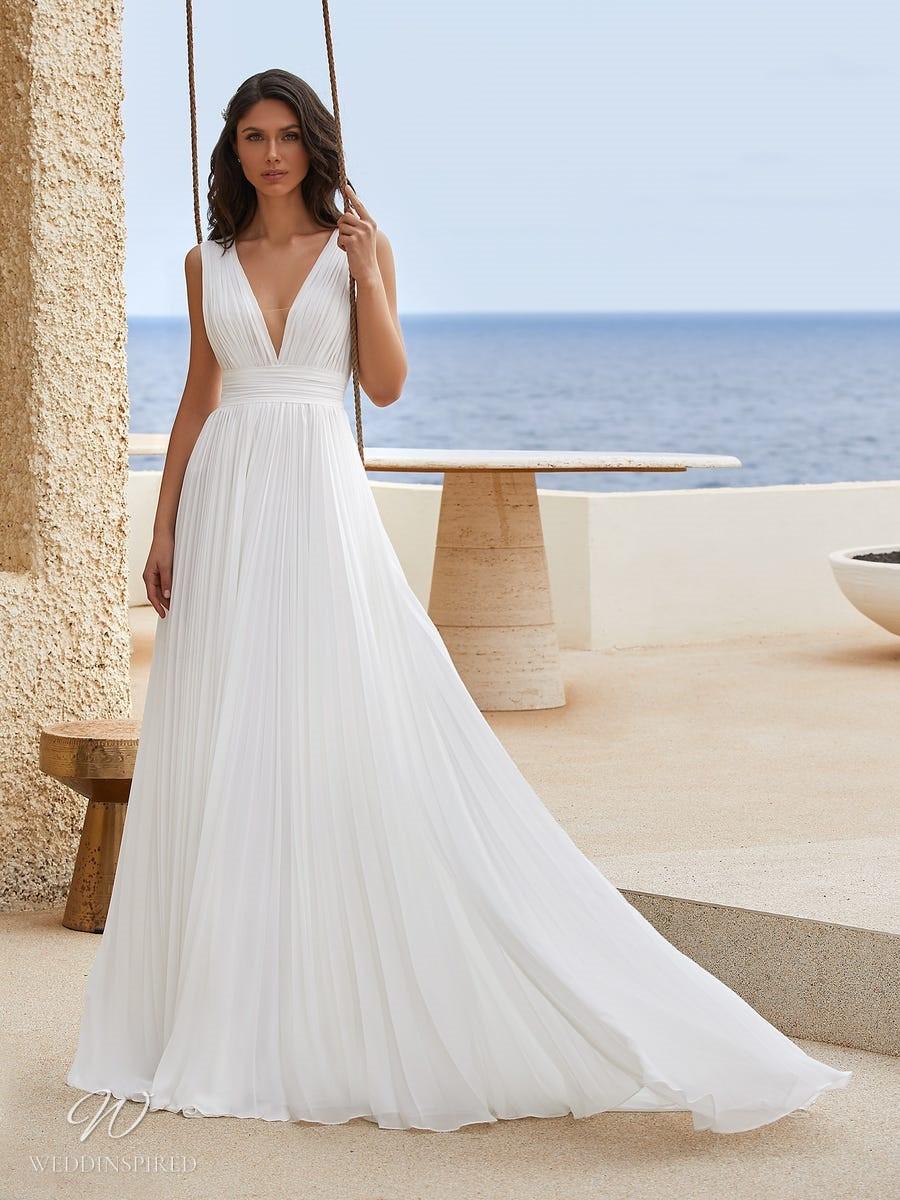 A Pronovias 2021 flowy Grecian style A-line wedding dress with a v neckline and pleats