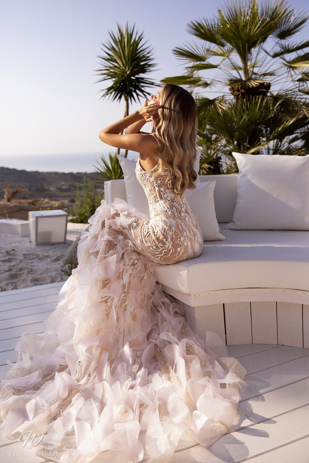 A Tina Valerdi blush lace fit and flare wedding dress with a ruffle skirt and lace