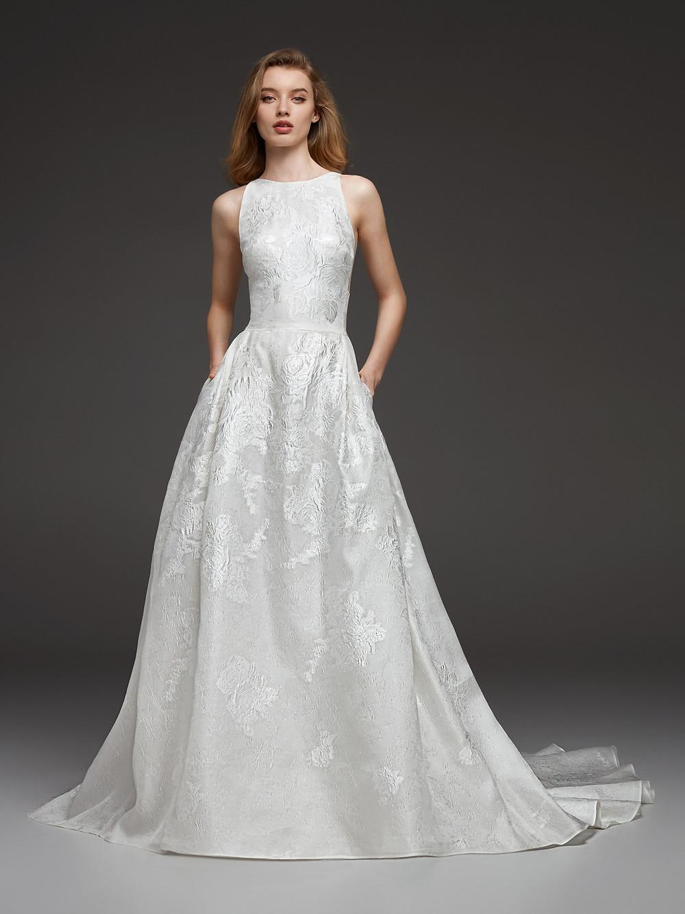 A Pronovias jacquard taffeta A-line wedding dress with pockets and a high neck