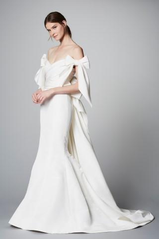 A Marchesa off the shoulder crepe mermaid fit and flare wedding dress with bows