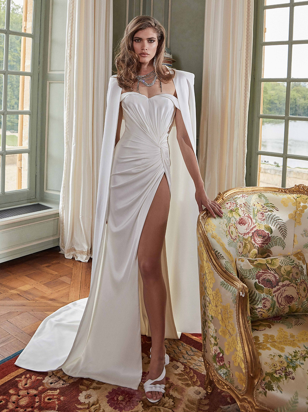 An elegant, silk satin, glass-like column wedding gown, expertly draped by hand. Features a thigh high slit and sexy off-the-shoulder straps