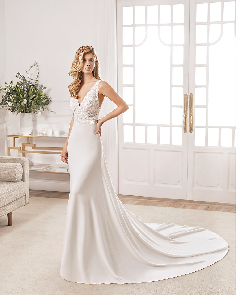 An Aire Barcelona 2020 lace and crepe mermaid fit and flare wedding dress with a v neckline and a train