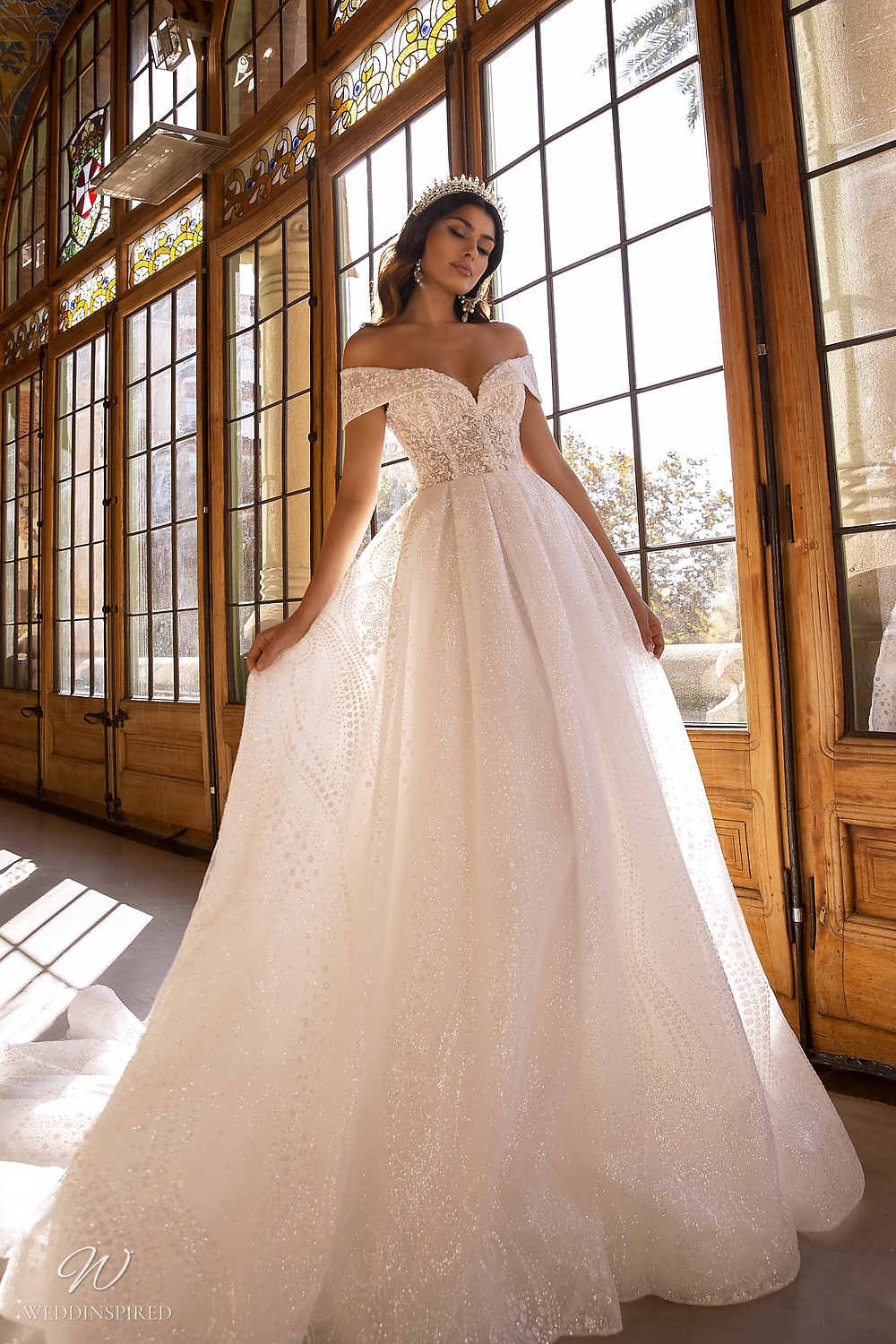 A Maks Mariano ivory off the shoulder sparkle princess ball gown wedding dress