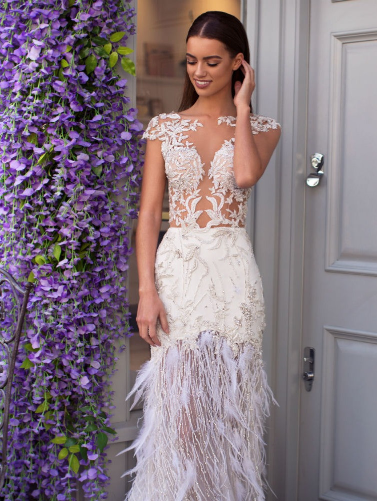 A Milla Nova lace and feather fitted wedding dress with an illusion top