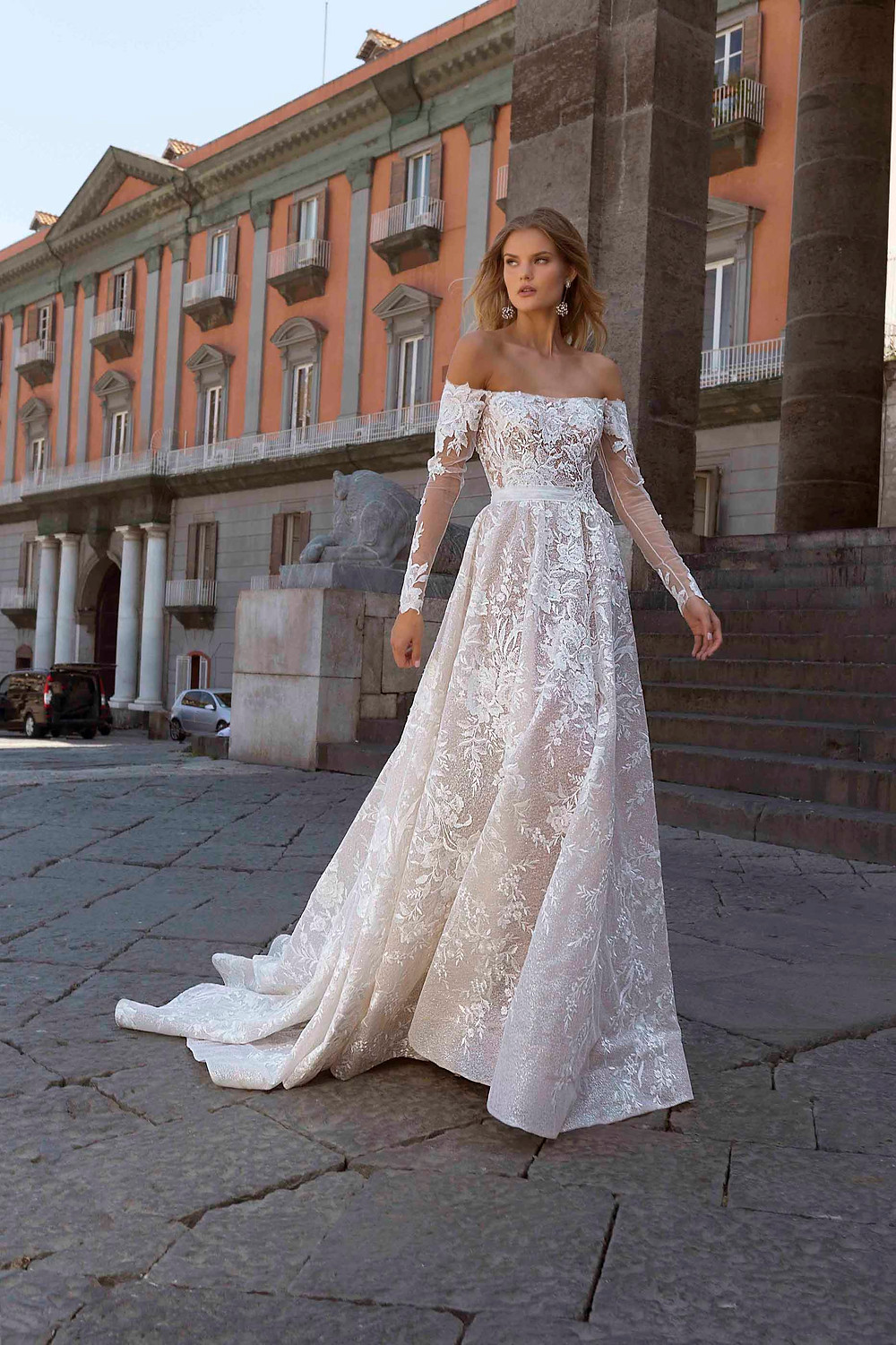 An off the shoulder, A-line wedding dress, with long illusion sleeves and lace